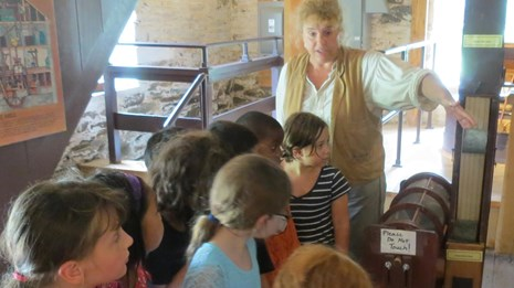 Jeanne, the miller, teaches students how the mill works