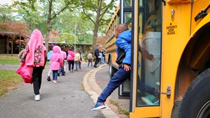 Stdents getting off of a bus outside the Rock Creek Park Nature Center