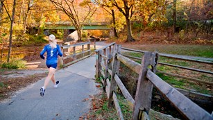 A woman runs on a trail by Peirce Mill in Rock Creek Park.