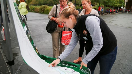A young volunteer at Rock Creek Park shows visitors where they are on a map.