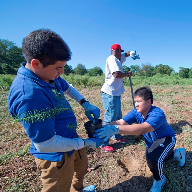 Two middle-school students plant native grasses in Military Field during National Public Lands Day.