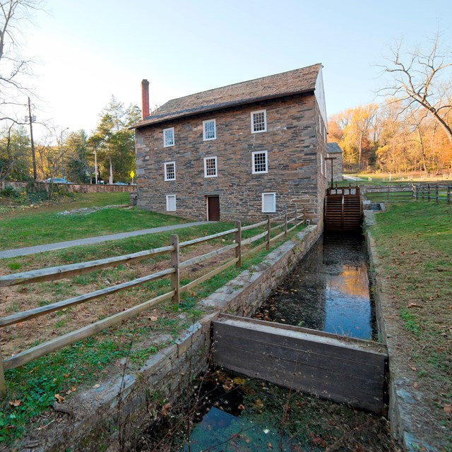 Peirce Mill from behind, the water wheel trough leads up to the building.