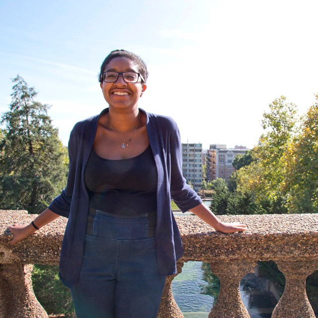 A young woman smiles as she stands on the top level of Meridian Hill Park.