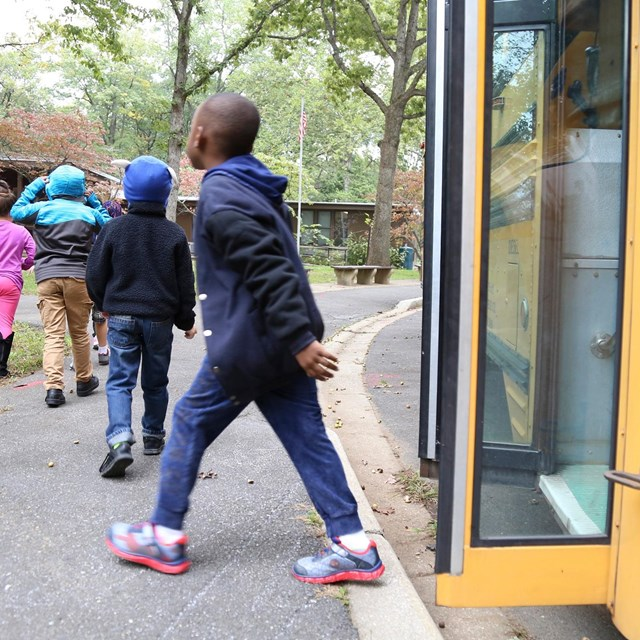 Kids getting off their yellow school bus at the Nature Center