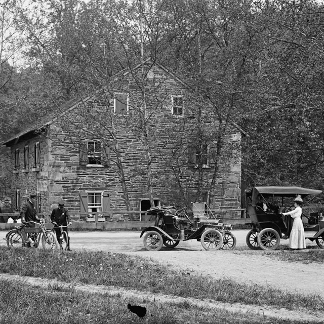 Historic photo of Peirce Mill with antique bicycles and automobiles in front