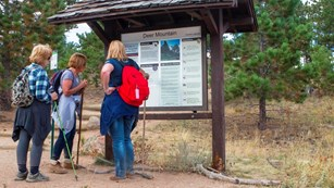 Three hikers standing in front of a trailhead sign