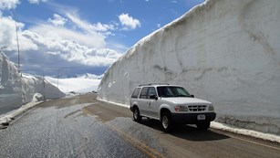 An SUV on the road beside a 15 foot tall snow drift