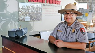 Image of female ranger at the front desk of the visitor center.
