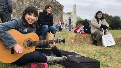 Woman plays acoustic guitar at Mission San Jose.