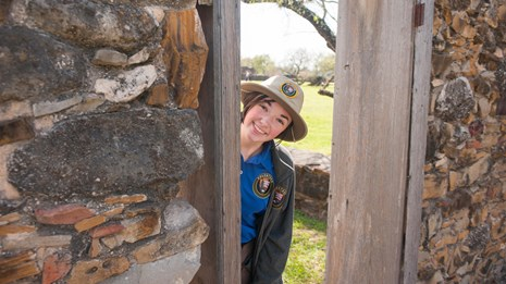 Youth volunteer peeks through a door at Mission San Jose.