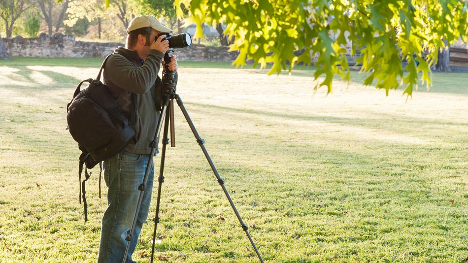 Visitor takes photographs at the park using a camera and tripod.