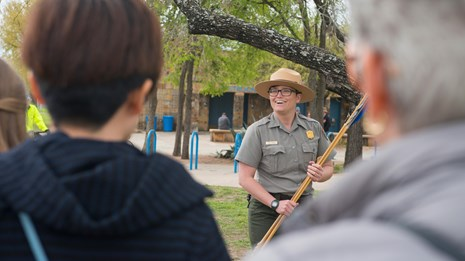 Park Ranger demonstrates the atl atl for a visiting field trip.