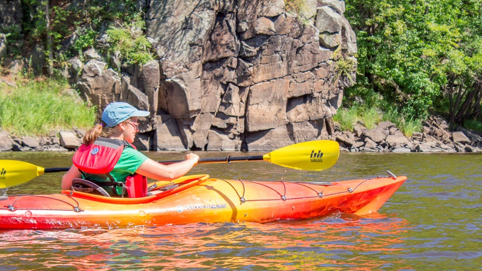 A kayaker paddles on a river with rocky bluffs.
