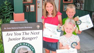 Three children hold certificates, badges, and patches from the Junior Ranger Program