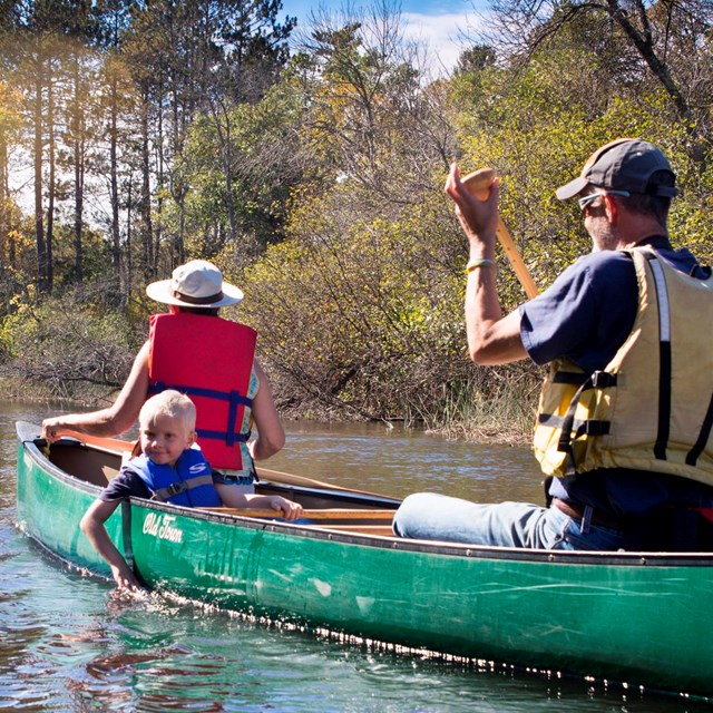 A family paddles in a canoe.