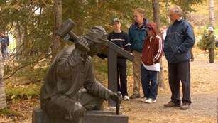 Visitors read about the winter of 1604-05 while looking at a bronze statue.
