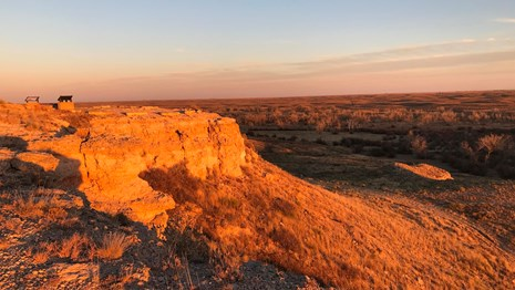 A rocky bluff overlooks the prarie, under a setting sun and warm light.