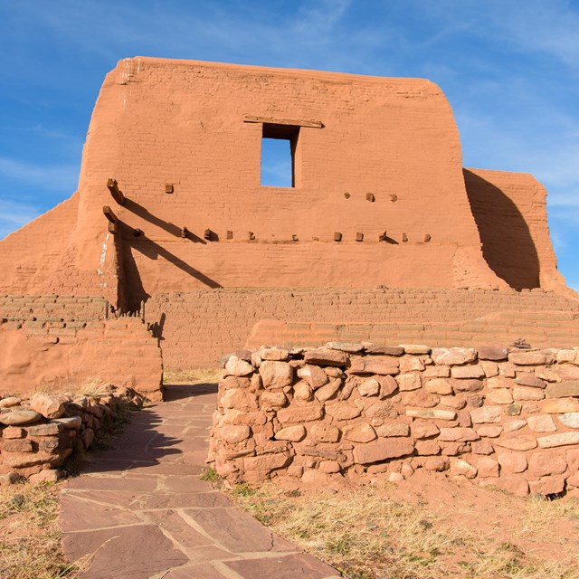 A large adobe historic church, with an adobe brick wall.