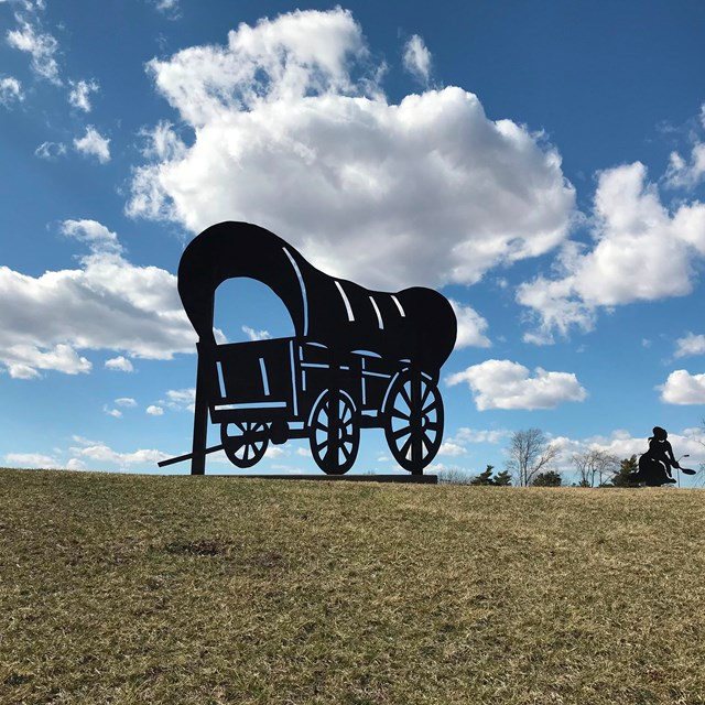 A silhouette of a covered wagon, on a grassy hill.