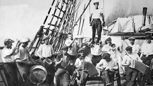 A group o sailors on the deck of sailing ship, seated and standing, holding musical instruments
