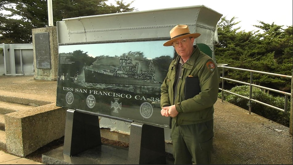 Park ranger standing outside beside a wayside exhibit showing the image of a ship