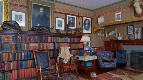 A room with books, portraits, and hunting trophies