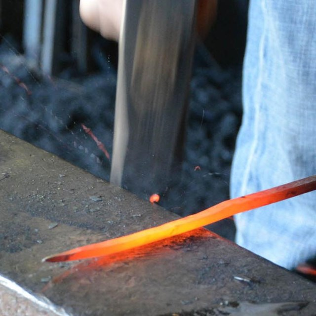 Blacksmith hammering orange-hot nail rod