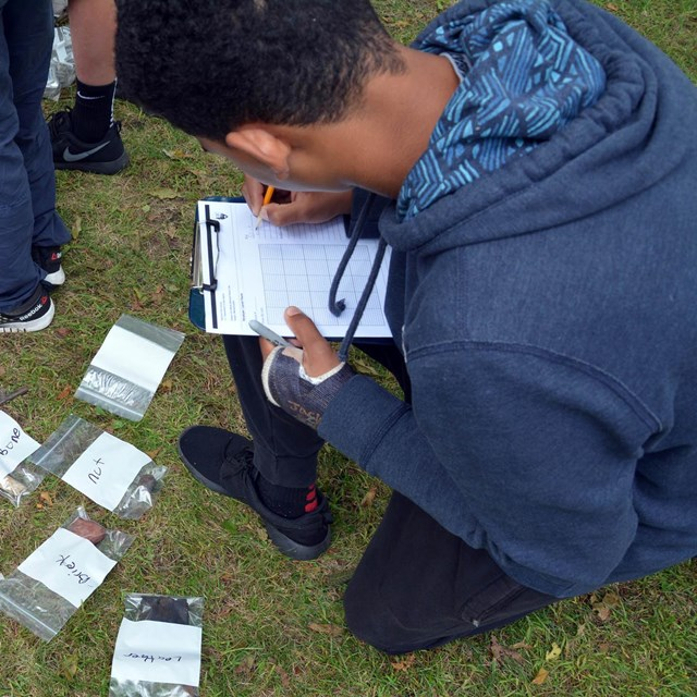 A student filling out a map in an archaeology program
