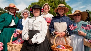 Volunteers dressed in historic garb smile while holding American flags.