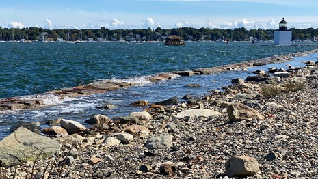 rocky shoreline with high winds making waves in the harbor and lighthouse and ships in the distance