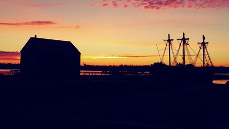 bright orange sunrise over Salem Harbor with land and structures appearing black