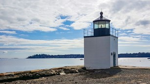light house on the edge of the water