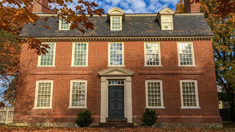 Two story brick house with many windows. Leaves on the ground indicate it is fall.
