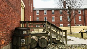barrels are in front of wooden stairs which lead up to the closed door of a brick building.