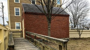 A wooden ramp leads to the side of a small brick building.