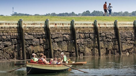 On the edge of a piece of land with grass, a row boat full of people is in the water.