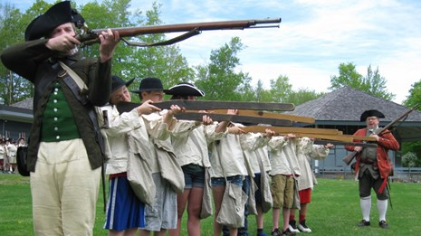 An 18th century soldier conducting musket drill with a group of students