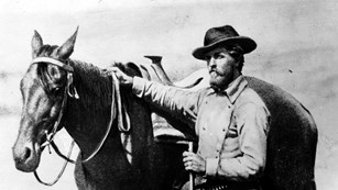 A black and white photo of a man standing next to a horse.