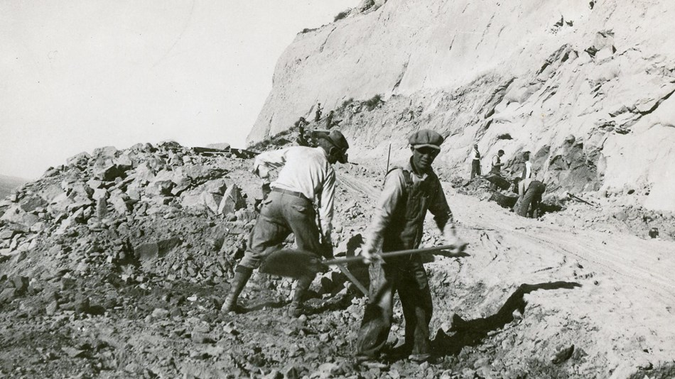 A black and white photo of men building a road with shovels.