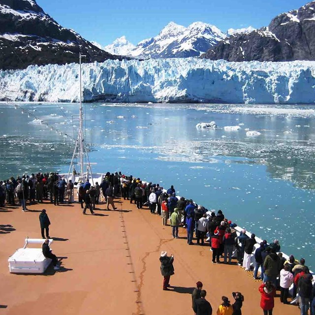 Visitors on a cruise ship view a tidewater glacier.