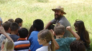 A ranger talks with a group of kids