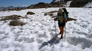 A hiker crossed a pitted snowfield