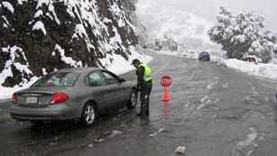 A ranger talks with a driver on a snowy roadway