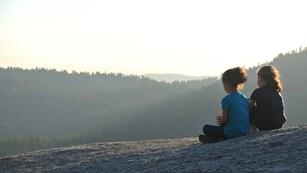 Two small children sit, enjoying the view. Photo by Tharwa Rabah.