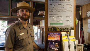 A ranger in uniform and flat hat stands at the information desk in the Kings Canyon Visitor Center.
