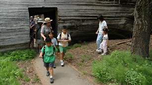A ranger leads a group through a doorway carved from a sequoia log