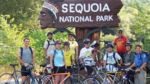 People with bicycles pose in front of the park entrance sign