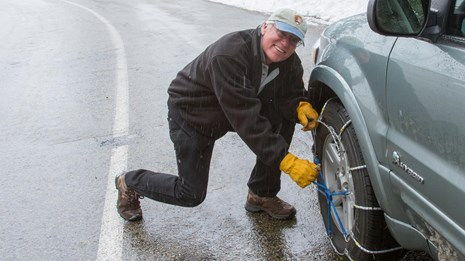 A man installs chains on his vehicle. Photo by Kirke Wrench.