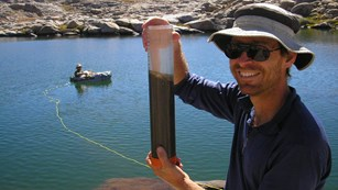 A researcher holds up a core sample near an alpine lake