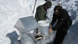 Two National Park Service scientists work on equipment to monitor precipitation chemistry.